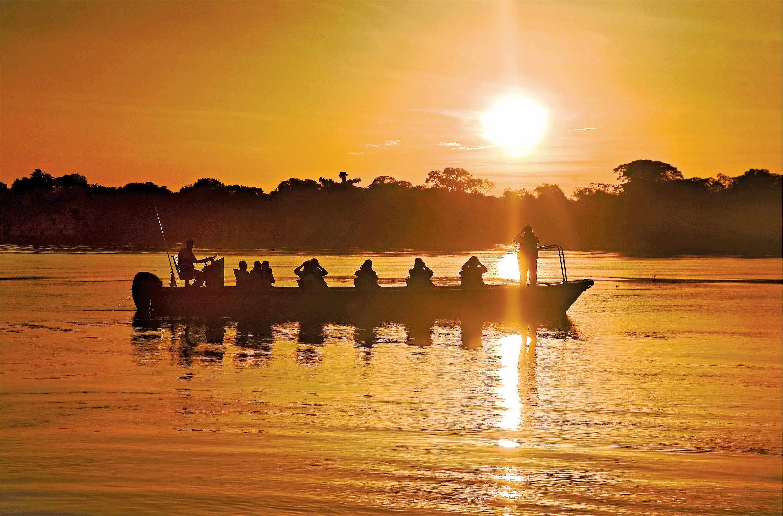 Lindblad Expeditions Delfin II Exterior Skiff Ride sunset.jpg